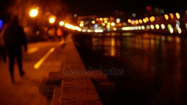 People stroll along the embankment strewn with evening lights. blur. 4K bokeh