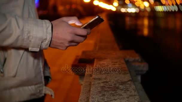 Un Uomo Si Trova Sul Lungomare E Utilizza Il Telefono Durante La Notte Su Uno Sfondo Di Luci Notturne 4k Sfocatura Dello Sfondo