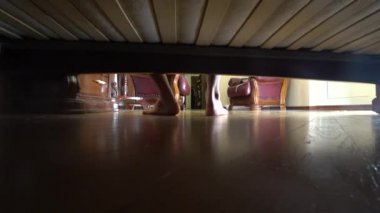 4k, the legs of a man. view from under the bed. the man climbs out of bed and leaves the bedroom
