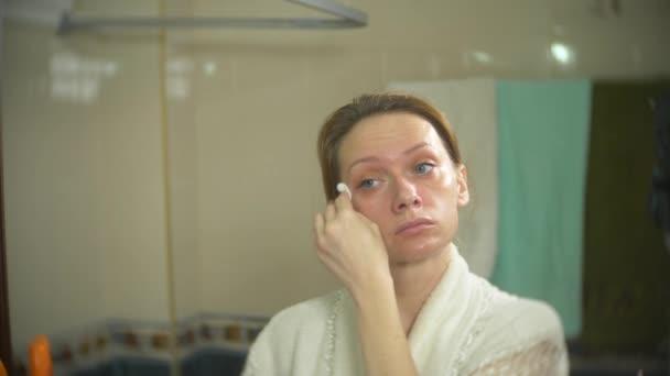 A nő arca előtt a tükör a fültisztító pálcikát tisztítás. 4k, lassú mozgás. közelről. életlenítés háttér.