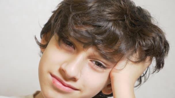 Mladý chlapec vypadá na kameru a usmívá se. 4 k. chlapec položil hlavu na jeho dlani a podíval se do kamery. Zpomalený pohyb