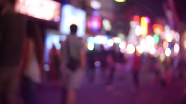 the movement of unrecognizable pedestrians walking through the city at night. Street background. 4k, blur