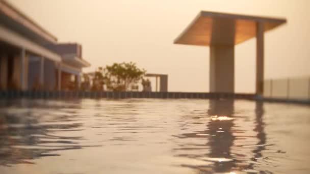 ein luxuriöser Pool auf dem Dach des Hauses mit Meerblick. am Sonnenuntergang. 4k, Zeitlupe, Sonnenblendung auf dem Wasser. Hintergrundunschärfe