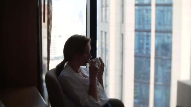 Krásná žena v bílé košili pití kávy k oknu s výhledem na panoráma města. 4k