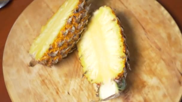 exotic fruits on the table. 4k, top view, slow motion. Pineapple sliced into pieces, rotates on a cutting board.
