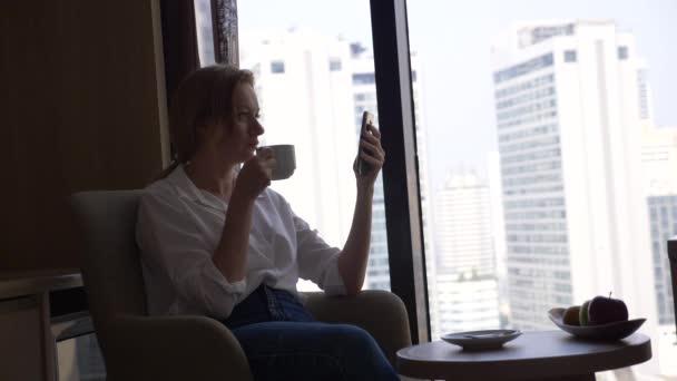 Krásná žena v bílé košili pití kávy u okna s výhledem na město. a pomocí svého smartphonu 4k