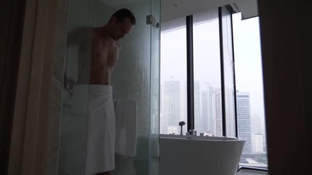 Mladý muž v koupelně. fešák se utřel ručníkem po sprše. 4k, pomalý pohyb