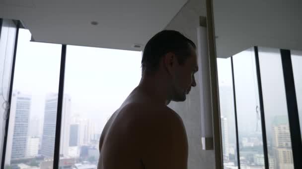 Pohledný muž použití břitvou v koupelně s výhledem z okna na mrakodrapy. 4k, pomalý pohyb