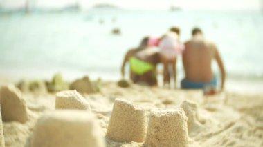 sand castle on the beach, an unrecognizable family makes a sand castle on a public beach. 4k, blur, slow-motion