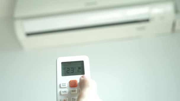 Die Klimaanlage ist eine drahtlose Fernbedienung in den Händen, die die Raumtemperatur reguliert. 4k, die Hand drückt die Tasten des Bedienfeldes auf dem Hintergrund der verschwommenen Klimaanlage
