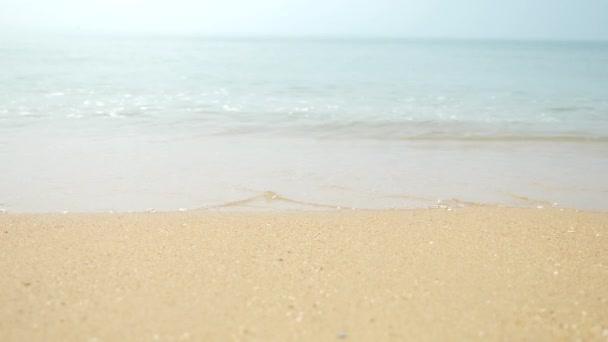 ženské nohy do písku, mořská vlna zahrnuje ženské nohy. 4k, pomalý pohyb