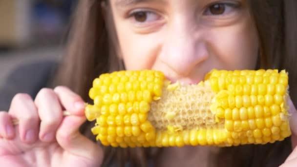 Legrační dívka dospívající jíst vařené kukuřice. 4 k, Zpomalený, detail.