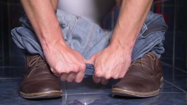 the feet of a man who sits in the toilet with a pain in his stomach. 4k, close-up, man in trousers and shoes in the toilet