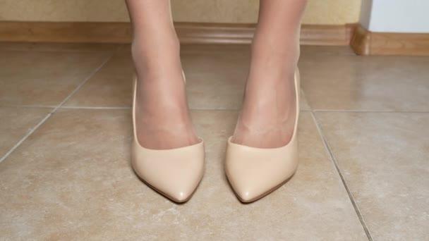 vyjádření emocí, řeč těla. žena šlape jí nohy na podlaze, rozhořčení, očekávání. detail. ženské nohy v krémové boty s vysokými podpatky. uvnitř. 4k