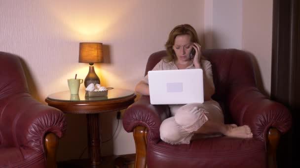 žena pracující v noci na notebooku a jíst občerstvení, sedí v křesle doma. 4k, pomalý pohyb.