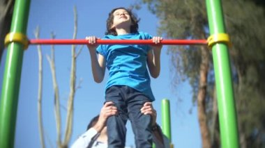 A handsome man in light clothes teaches a boy in a blue T-shirt how to pull himself up correctly on a horizontal bar in a summer sunny park, 4k, slow motion
