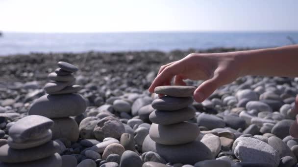 közeli, a kéz bedobja a piramis kövek a tengerparton. 4k, lassú mozgás