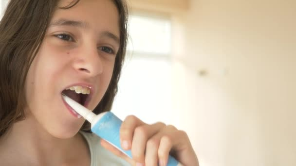 The child cleans his teeth in front of a mirror in 4k. girl teenager brushes teeth with electric toothbrush, close-up, slow-motion shooting