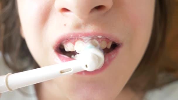 Dítě čistí zuby před zrcadlem v rozlišení 4 k. dospívající dívka čistí zuby s elektrický kartáček na zuby, close-up, zpomalené střílení