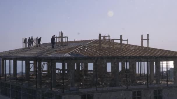 Unerkennbare Bauarbeiter und Zimmerleute, die auf dem Dach arbeiten. ein blauer bewölkter Himmel vor dem Hintergrund des Meeres. 4k, Zeitlupe
