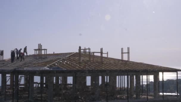 K nepoznání stavební a tesařské práce na střeše. Modrou oblohou na pozadí moře. 4k, pomalý pohyb