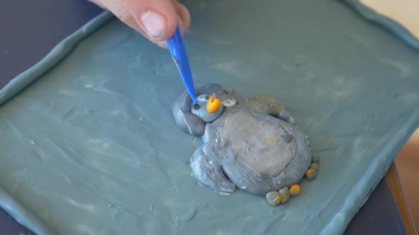 dívka sedí u stolu, nakreslí různé postavy z plastelíny barevný model. Vývoj umění modelování u dětí. 4 k, close-up, pomalý pohyb