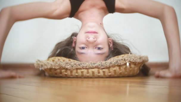 Vtipná holka dělá vzhůru dolů kliky v domě. 4 k. portrét dívky stojící vzhůru nohama