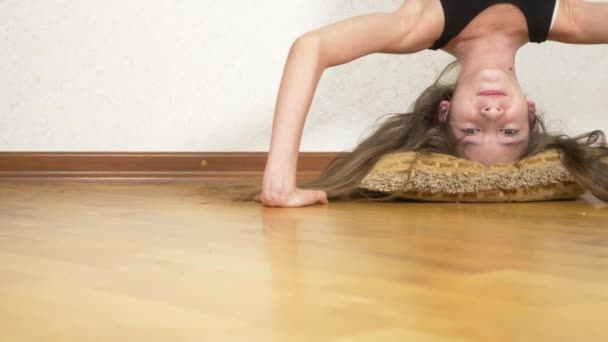 funny girl doing upside down pushups in house. 4k. portrait of a girl standing upside down