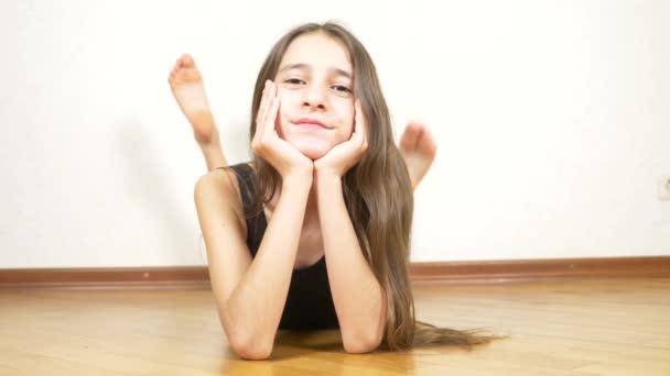 Dívka leží na podlaze v tělocvičně a usmívá se na fotoaparát, 4k.