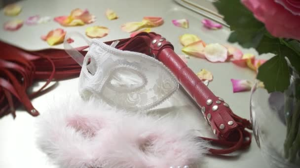Pelz, Handschellen und Spitze Maskerade Maske. schöne exquisite Sex-Spielzeug für Erwachsene auf dem Tisch neben dem Spiegel im Schlafzimmer. 4k, Slow-motion