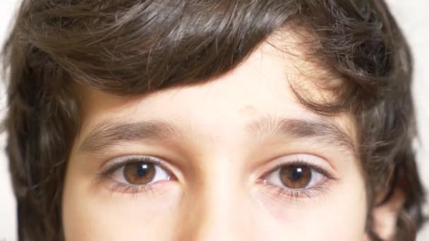 A barna szem a fiú hosszú, fekete szempillák. úgy néz ki, egy hosszú göndör üstök alatt. 4 k, lassú mozgás, közelkép
