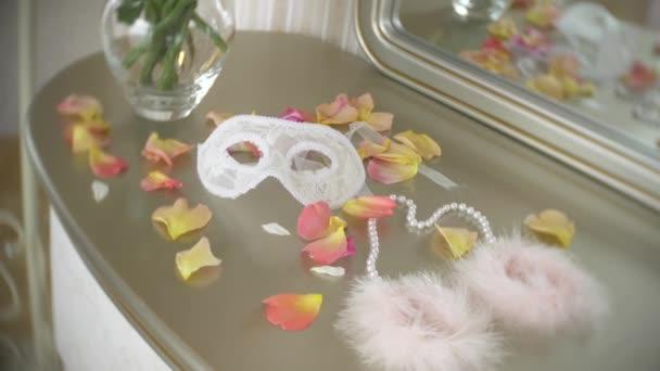 Pelzhandschellen und Maskenmaske aus Spitze. schöne exquisite Sexspielzeuge für Erwachsene auf dem Tisch neben dem Spiegel im Schlafzimmer. 4k, Zeitlupe,