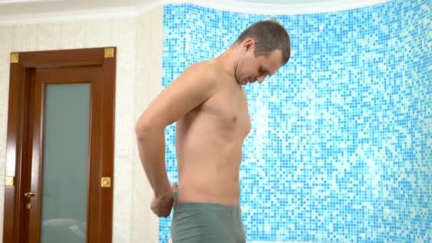 Fehér fiatalember méri a testet mérőszalaggal, miközben a fürdőszobában áll. humoros fogalom