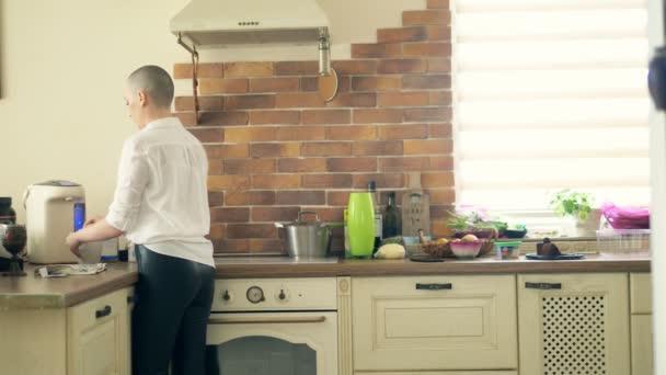 Střední střela. Stylová plešatá žena pije horký nápoj, zatímco stojí v kuchyni doma.