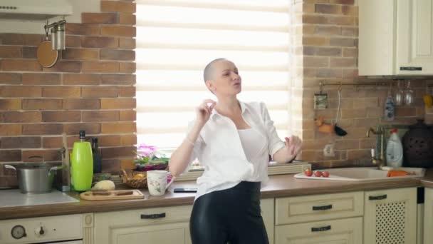 Střední střela. mladá úžasně emocionální plešatá žena tančí v kuchyni doma