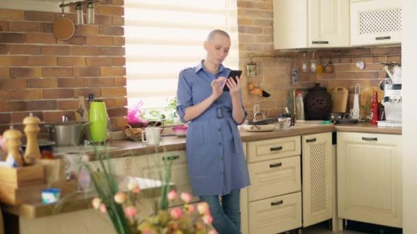 Střední střela. stylový plešatý žena pomocí mobilu v kuchyni doma