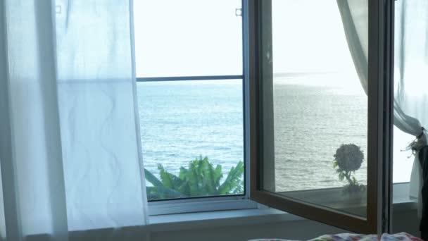 Průhledná opona na okně s výhledem na moře, jemně pohnutá větrem. Sluneční světlo.