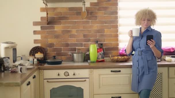 Střední střela. stylová žena používající mobilní telefon v kuchyni doma