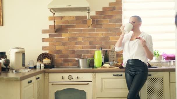 közepes lövés. Stílusos kopasz nő iszik egy forró italt, miközben otthon áll a konyhában.