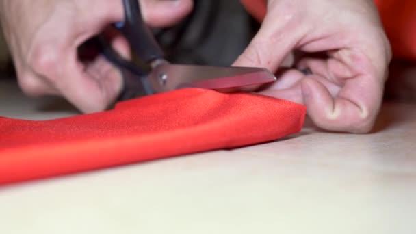 Közelkép. férfi szabók kéz vágott vörös szövet ollóval