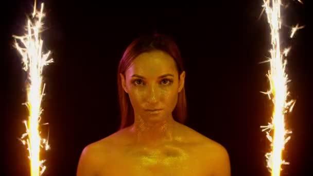 krásná dívka tvář s třpytkami na tváři mezi jiskry na černém pozadí