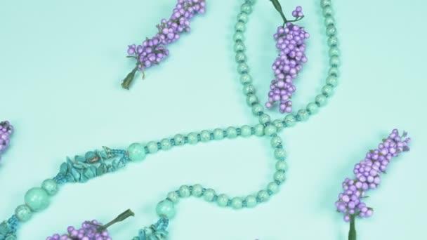 náhrdelník z tyrkysové a umělé levandulové květy na modrém pozadí