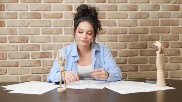 artist girl draws a pencil sketch from a wooden figure of a man