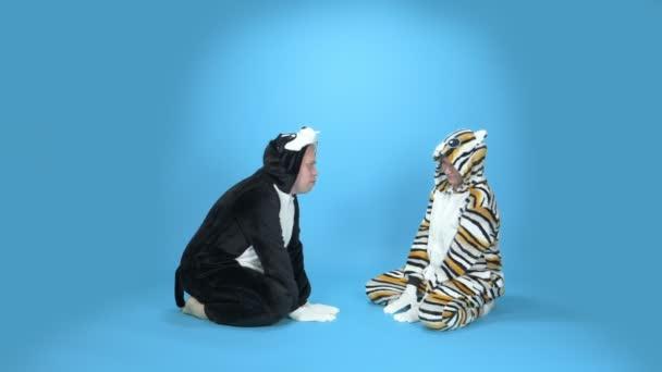Katze und Hund. eine Frau und ein Mann in einem kigurumi Katze und Hund. blauer Hintergrund