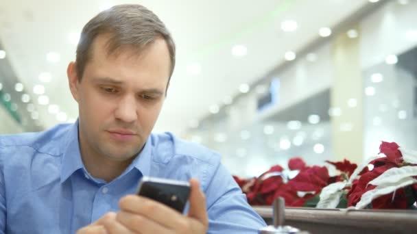 mladý pohledný muž překvapený při použití smartphone při posezení v kavárně