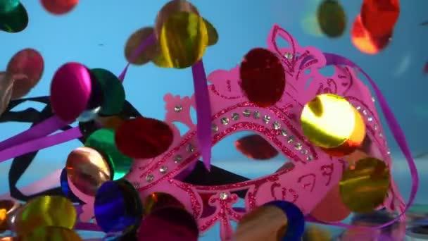 konfety, maškarní maska a hadovitá pod vodou na modrém pozadí