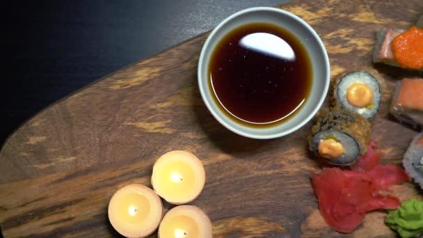 Romantikus vacsora. Japán ételek és gyertyák fából készült tányéron. Gyönyörű ételkompozíció gyömbérrel, haltekercsekkel, wasabival és szójaszósszal. Kilátás felülről.