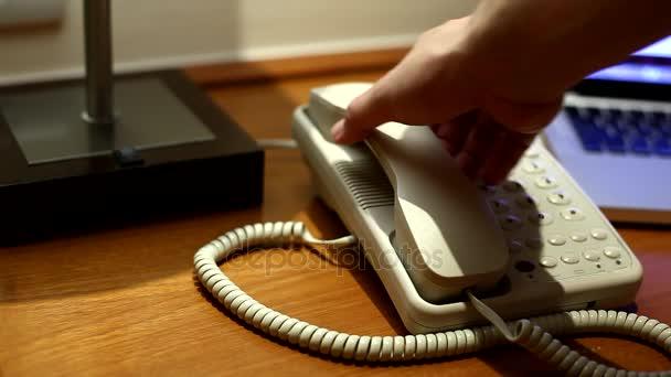 Bílý telefon zvoní v místnosti