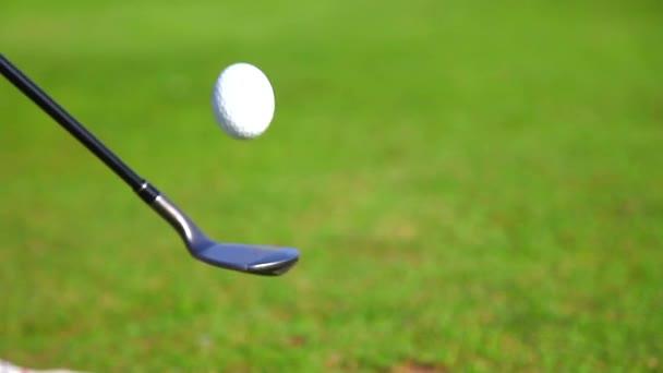 Golfista skákací golfový míček na klubu