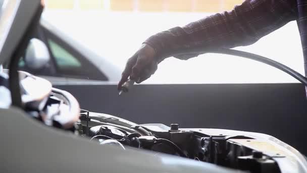 Autószerelő keze tiszta és tisztítása a motor ventilátor a garázsban